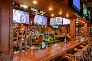 wooden sports bar with multiple tv screens